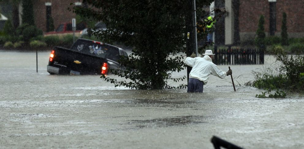 PHOTO: A vehicle and a man try to navigate floodwaters in Florence, S.C., Oct. 4, 2015, as heavy rain continues to cause widespread flooding in many areas of the state.