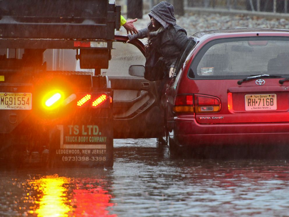 A woman is rescued from rising water after her Toyota Camry station wagon stalled out on West Fort Lee Rd as she approached the Hackensack River Tuesday morning, Dec. 9, 2014, in Bogota, N.J.