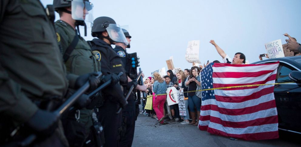 PHOTO: Protesters opposed to Republican presidential candidate Donald Trump are separated from supporters by a line of riot police officers outside Trumps campaign rally in Costa Mesa, Calif., April 28, 2016.