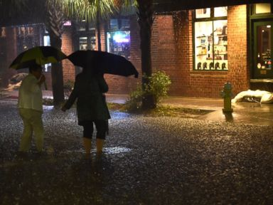 PHOTO: Two women cross a flooded street in downtown Charleston, SC on October 03, 2015.