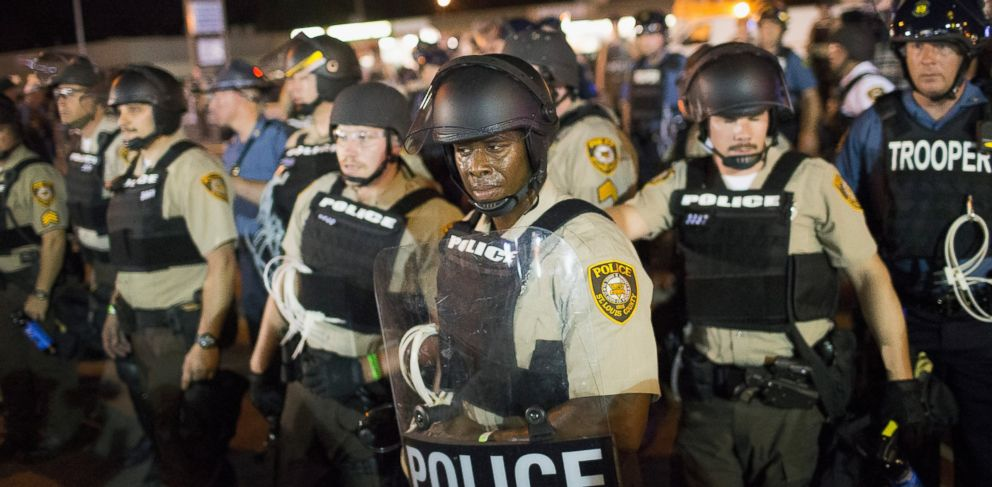 PHOTO: Police stand guard as demonstrators, marking the one-year anniversary of the shooting of Michael Brown, protest along West Florissant Street, Aug. 10, 2015 in Ferguson, Mo.