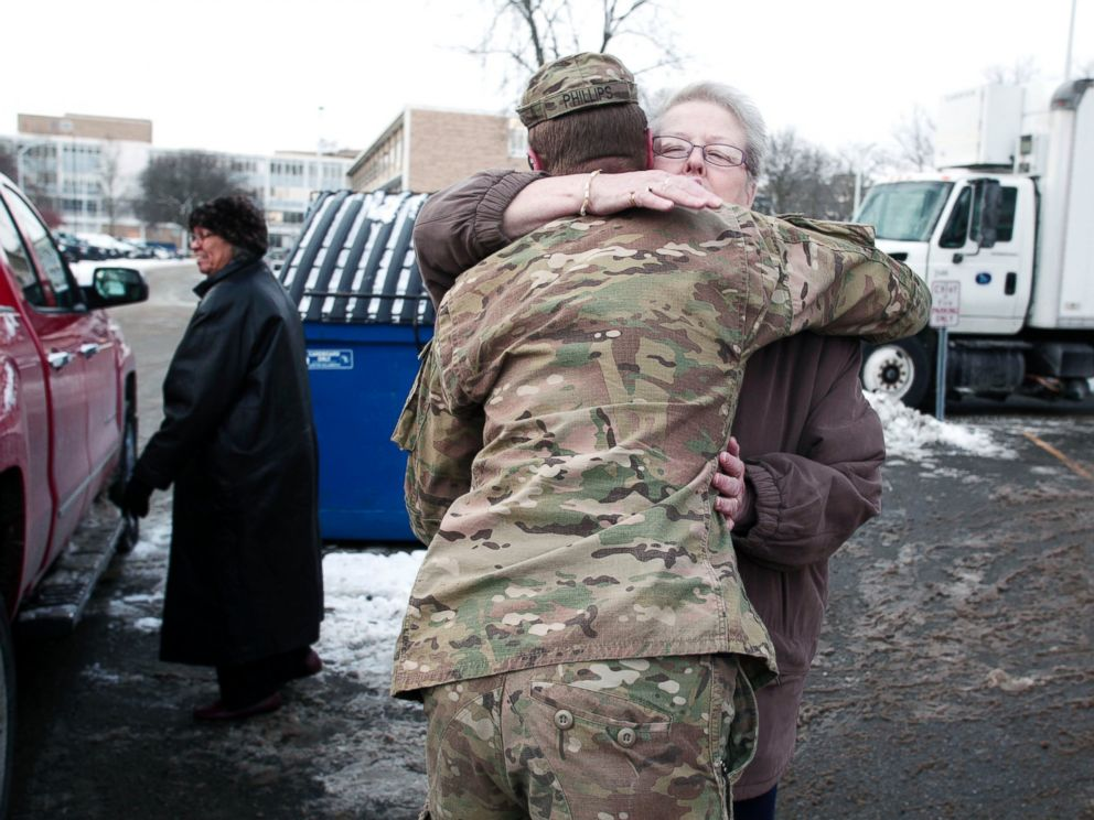 PHOTO: Michigan National Guard Staff Sergeant William Phillips gets a hug from a Flint resident after helping her carry bottled water to her car at a Flint Fire Station on Jan. 13, 2016 in Flint, Mich.