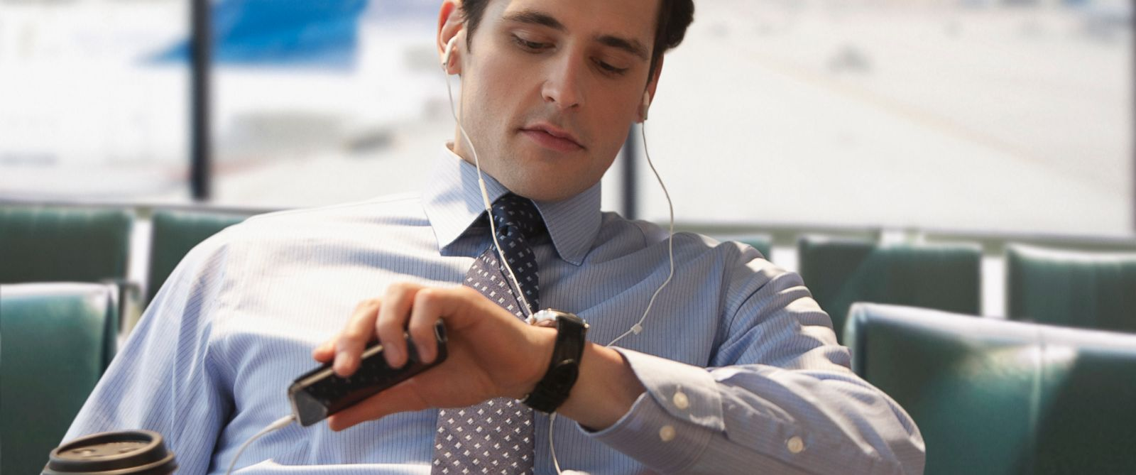 PHOTO: A business man checks the time at airport while using his cell phone.