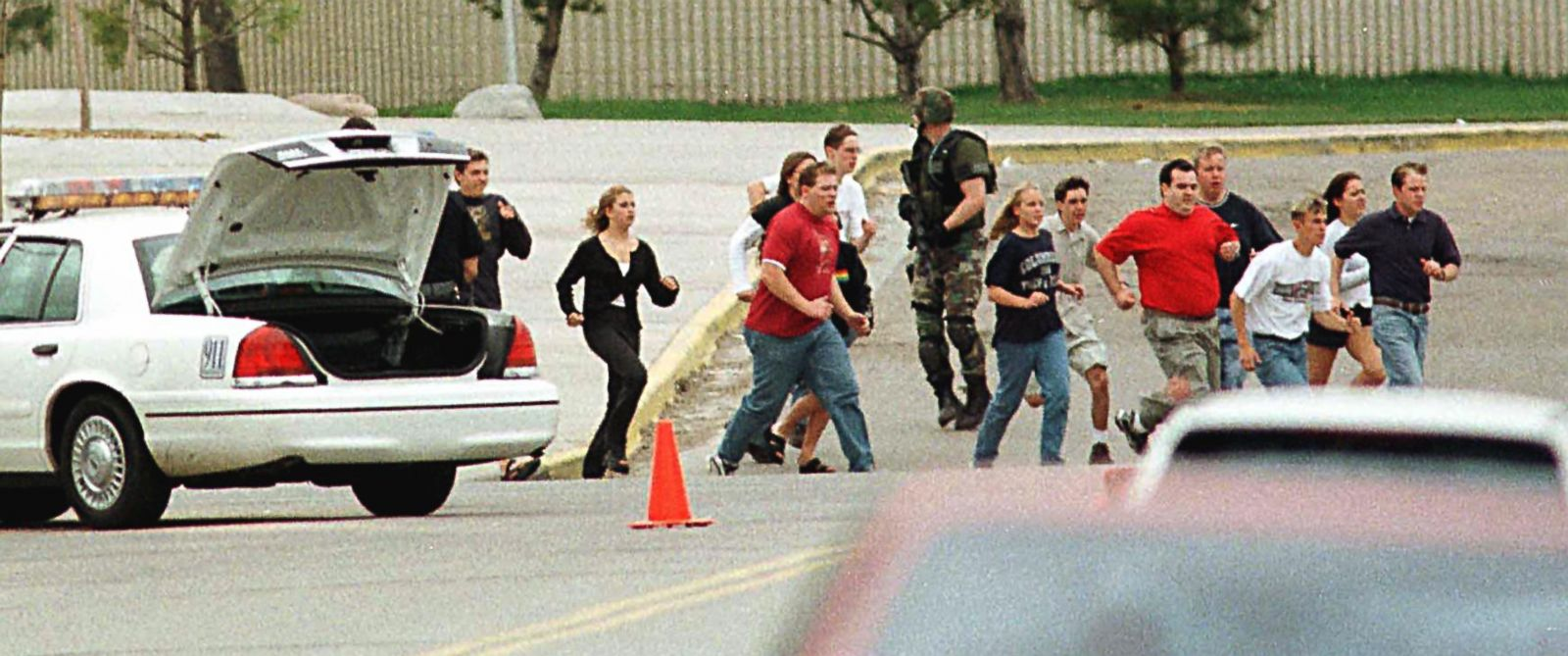 PHOTO: Students from Columbine High School run under cover from police in Littleton, Colo.