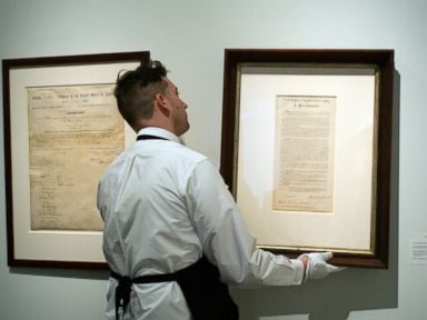 PHOTO: An employee adjusts a display of two significant and foundational documents of the US, the Emancipation Proclamation and the 13th Amendment signed by President Abraham Lincoln, to be auctioned at the Sothebys in New York, May 18, 2016.