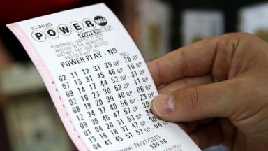 PHOTO: A customer at a 7-Eleven store checks the numbers on his Powerball lottery ticket in Chicago, Aug. 7, 2013.