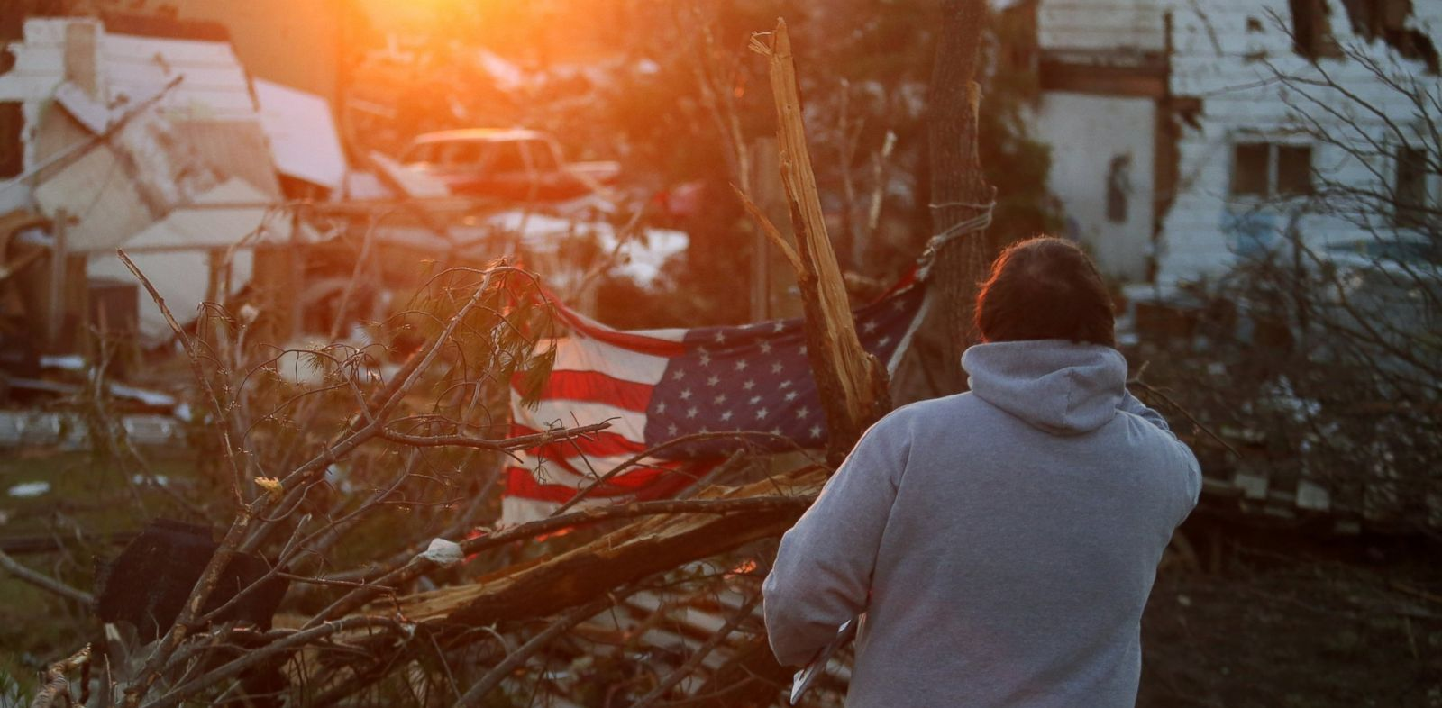 PHOTO: A person stands amongst damaged buildings along Washington Road in the aftermath of a tornado, Nov. 18, 2013 in Washington, Ill.