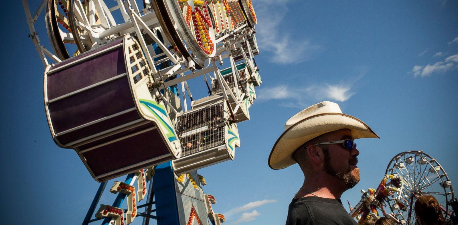 PHOTO: A man stands beneath a ride at the North Dakota state fair, July 27, 2013, in Williston, North Dakota.