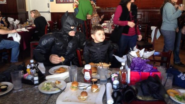 PHOTO: Miles Scott, better known as Batkid, takes a break for lunch with a grown-up Batman