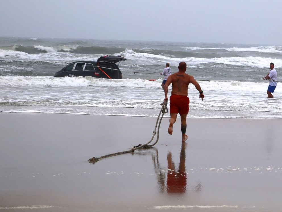 PHOTO: A lifeguard runs in to the ocean to rescue a family after a mother drives her car in to the ocean, March 5, 2014 in Daytona Beach, Fla.
