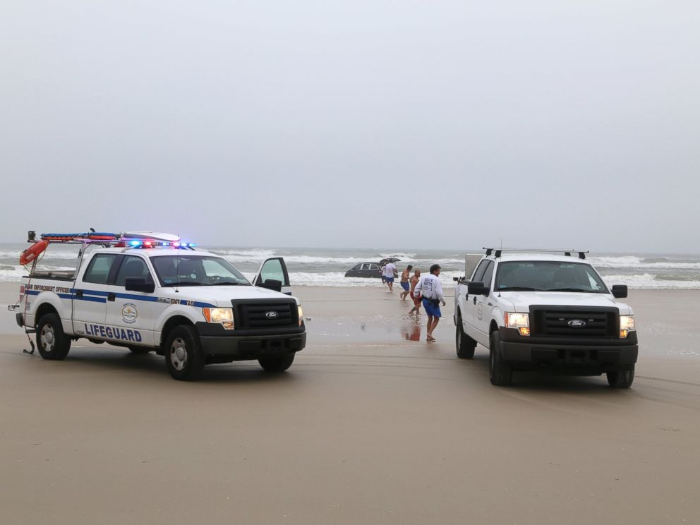 PHOTO: Lifeguards on scene to help rescue a family after a mother drives her car in to the ocean, March 5, 2014 in Daytona Beach, Fla.