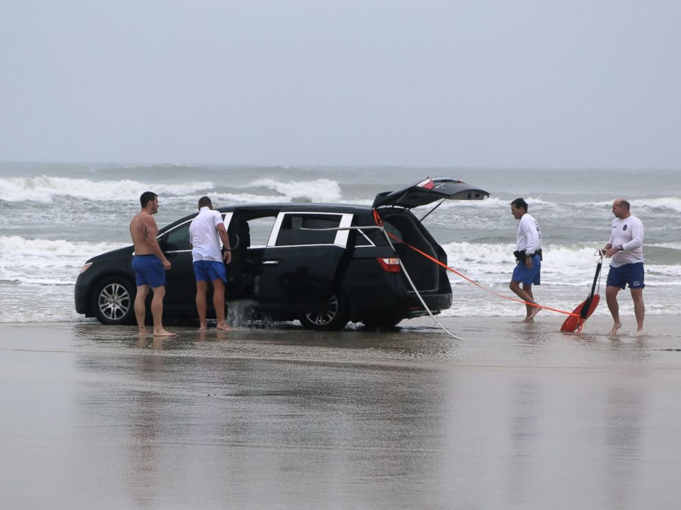 PHOTO: A family is rescued after a mother drives her car in to the ocean, March 5, 2014 in Daytona Beach, Fla.
