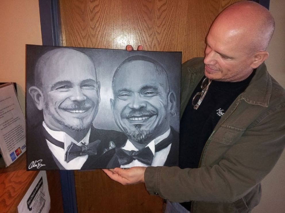 PHOTO: A pleased client picks up the portrait of his late husband painted with traces of his ashes.