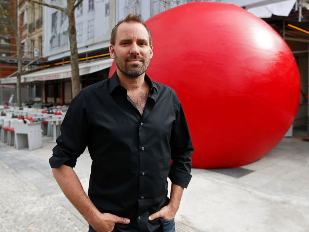PHOTO: Artist Kurt Perschke poses with his huge red ball as part of his RedBall Project in Paris on April 18, 2013.