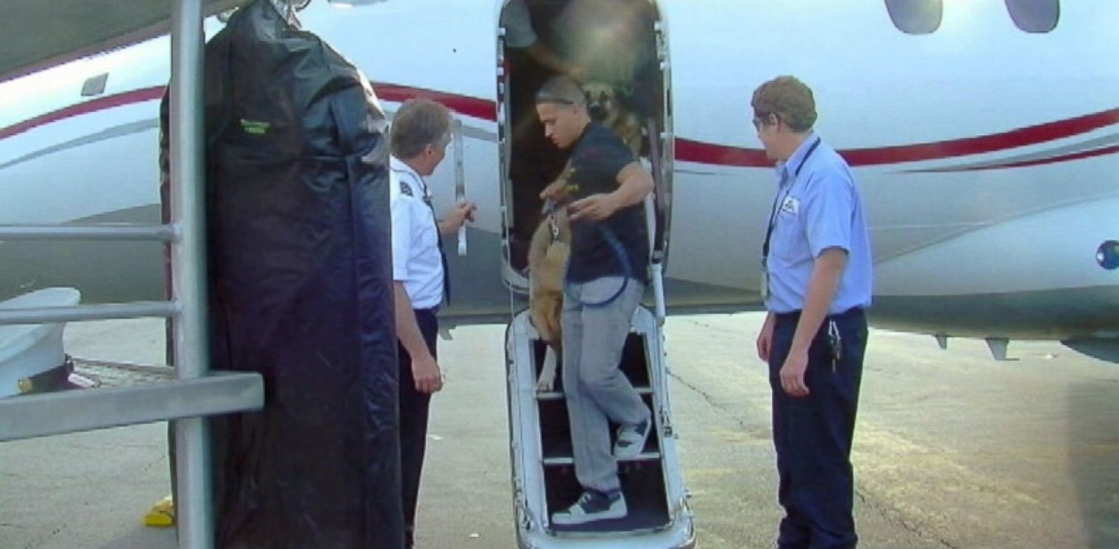 PHOTO: Andrew Morales, with Dusty and Wyatt, step off the chartered plane.