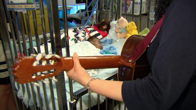 PHOTO: Music therapist Rebecca Loveszy serenades little Jadion, who was born with a heart defect.