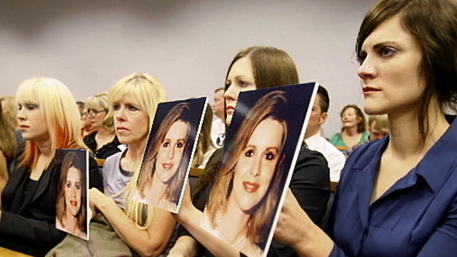 PHOTO: The daughters of Martin MacNeill hold up pictures of their dead mother during his first court appearance, Aug. 27, 2012.