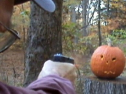 VIDEO: A man uses his gun to decorate a pumpkin with a face.