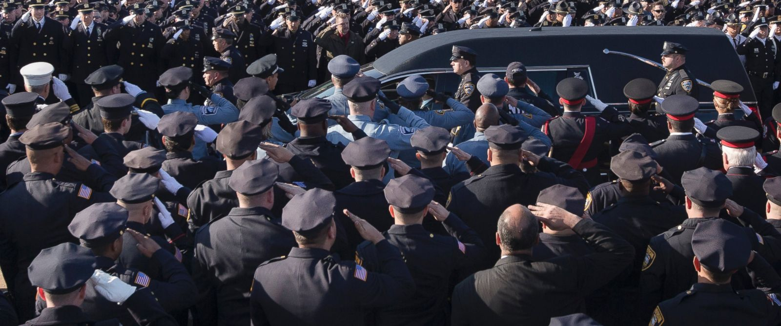 PHOTO: Police officers salute as the hearse of New York city police officer Rafael Ramos drives along his funeral procession route in the Glendale section of Queens, Saturday, Dec. 27, 2014, in New York.