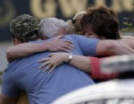 PHOTO: A group of people huddle together after an explosion and gunshots were heard near the scene where a man was holding four firefighters hostage Wednesday, April 10, 2013 in Suwanee, Ga.