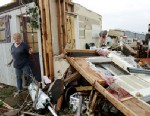 PHOTO:Marlena Hodson walks out of her home as her grandsons, Campbell Miller, 10, and Dillon Miller, 13, at right, help her sort through belongings after a tornado damaged her home Carney Okla., on Sunday, May 19, 2013.