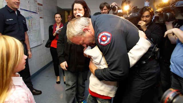 PHOTO: Rebecca Quintanilla, center left, wipes tears from her face as her adopted son Koregan, 10, hugs Arlington Fire Fighter Wesley Keck, center right, as the two meet Nov. 15, 2012, in Arlington, Texas.