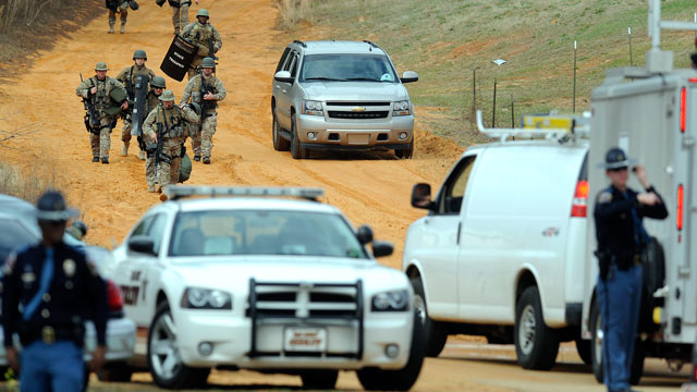 PHOTO: Heavily armed men move away from the suspects home at the scene of a Dale County hostage scene in Midland City, Ala., Jan. 30, 2013.