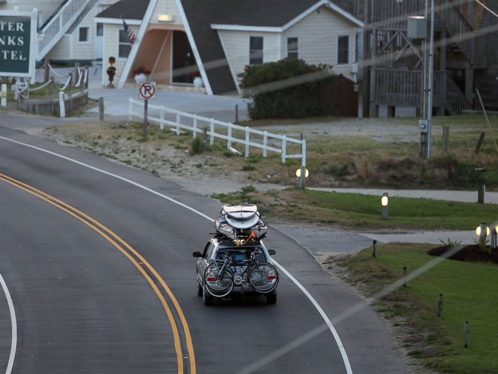 PHOTO: A car loaded down with bikes, kayaks and surfboards heads north on NC 12 through Buxton on Hatteras Island, N.C., July 3, 2014.