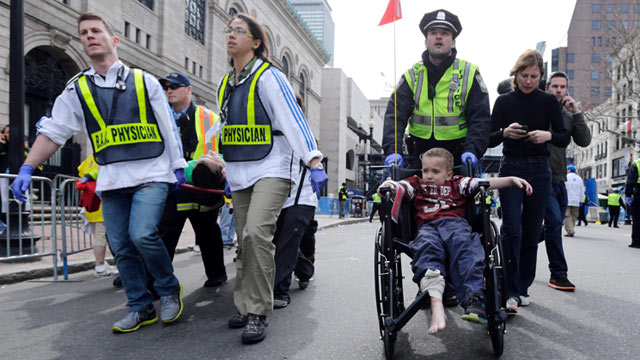 PHOTO: A Boston police officer wheels in injured boy down Boylston Street as medical workers carry an injured runner following an explosion during the 2013 Boston Marathon in Boston, April 15, 2013.