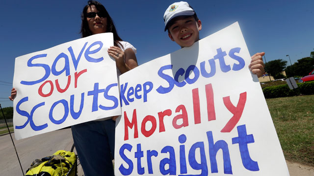 PHOTO: A protester stands with her son, as they hold signs near where the Boy Scouts of America are holding their annual meeting, May 22, 2013, in Grapevine, Texas.