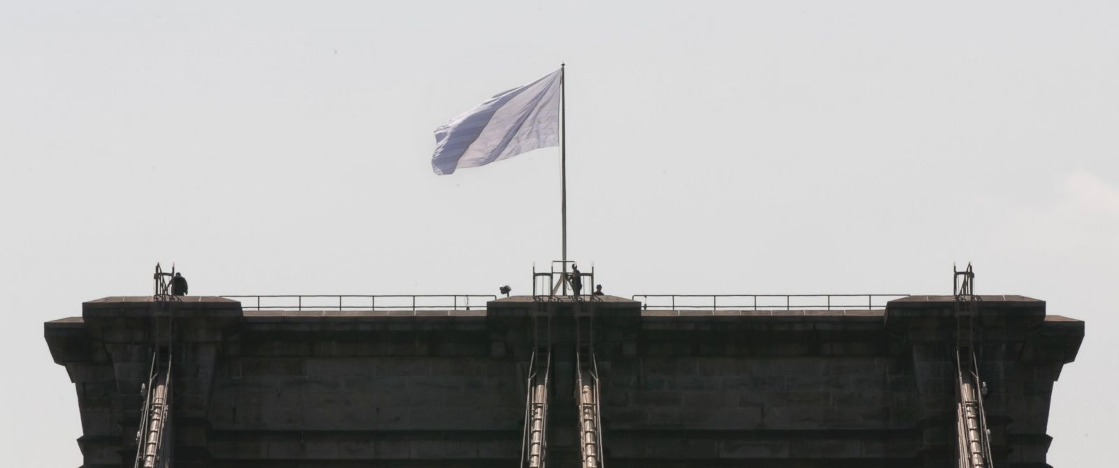 PHOTO: New York City police officers stand at the base of a white flag flying atop the west tower of the Brooklyn Bridge, July 22, 2014.