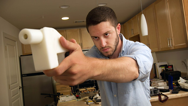PHOTO: Cody Wilson poses with the plastic pistol that he created with a 3-D printer, at his home in Austin, Texas, May 10, 2013.
