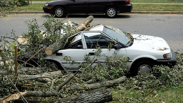 PHOTO: A car sits crushed by a fallen tree on Carrington Road in Lynchburg, Va. on July 1, 2012.