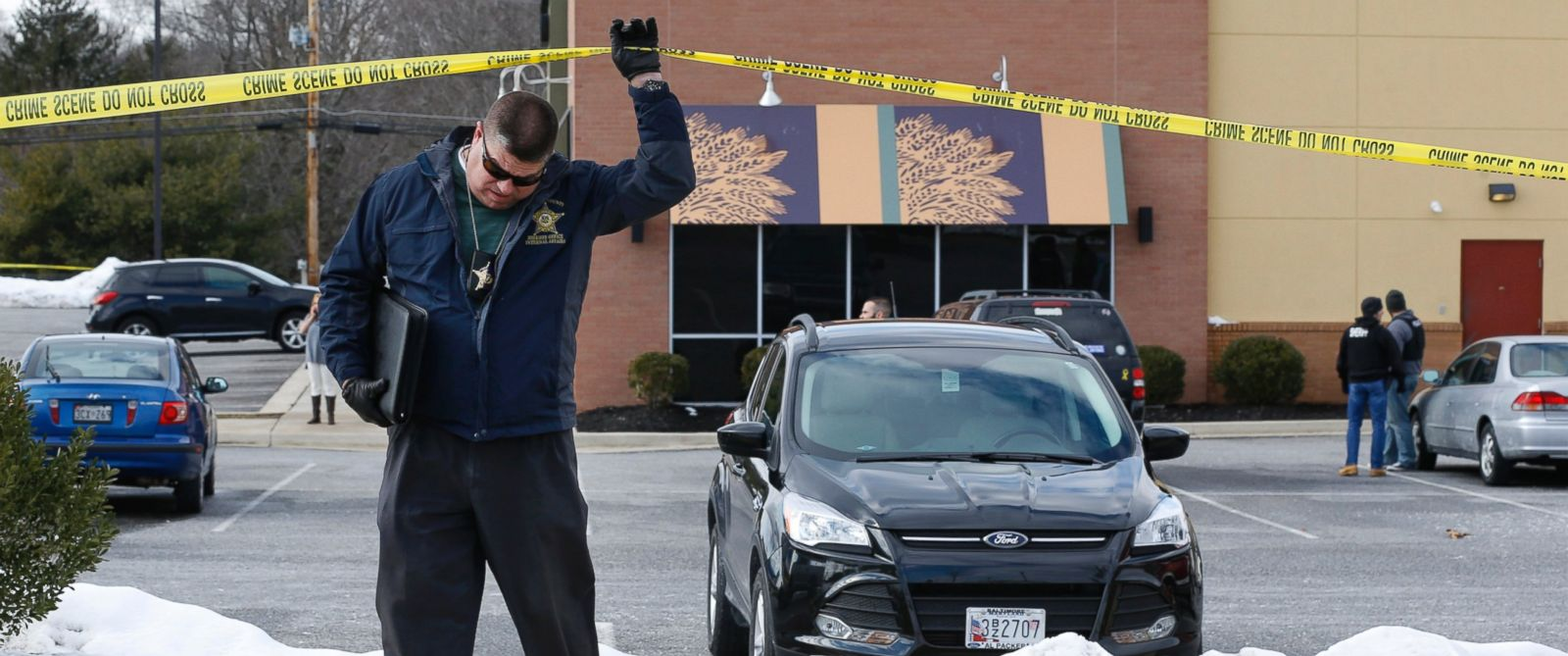 PHOTO: An investigator walks beneath a police tape line at the scene of a shooting at a shopping center in Abingdon, Md., Feb. 10, 2016.