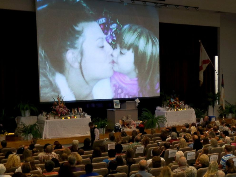 PHOTO: Photos of Sarah Spirit and her children are displayed on the screen during a memorial service at Bell High School Don Spirits family on Sept. 21, 2014, in Bell, Fla.