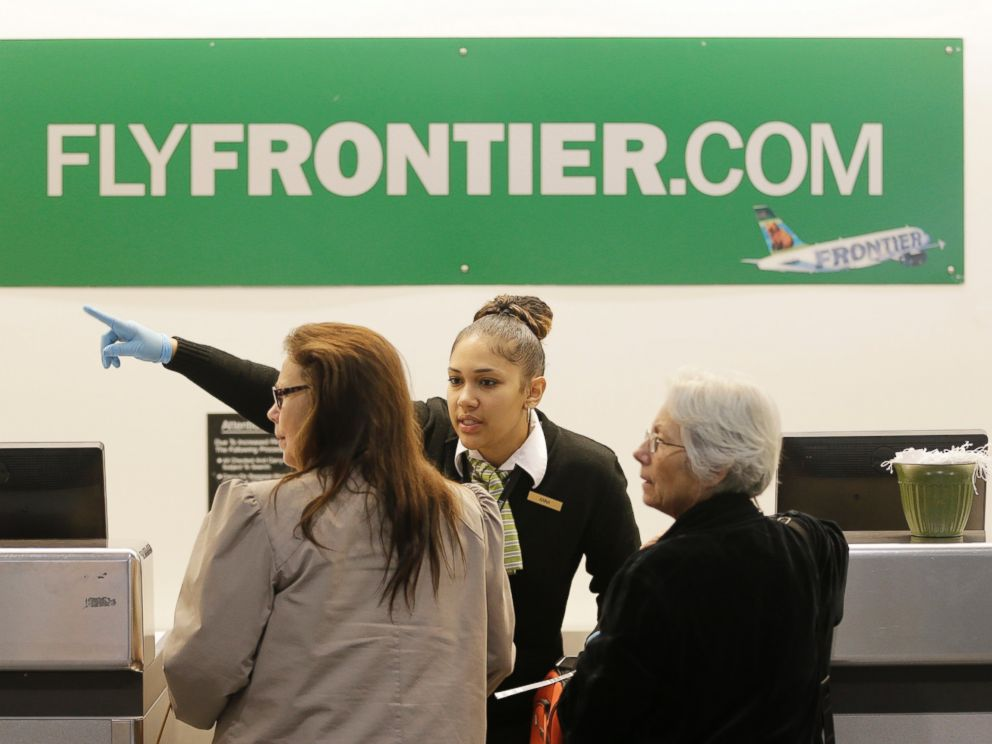 PHOTO: A Frontier Airlines employee wears rubber gloves as she directs passengers where to go at Cleveland Hopkins International Airport, Oct. 15, 2014, in Cleveland.