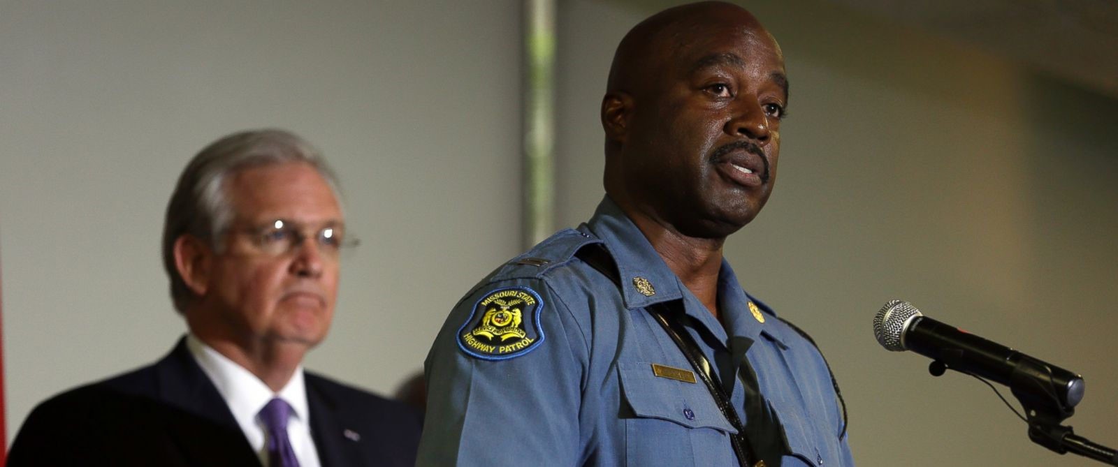 PHOTO: Capt. Ron Johnson of the Missouri Highway Patrol speaks during a news conference as Missouri Gov. Jay Nixon listens during news conference on Aug. 14, 2014, in St. Louis.