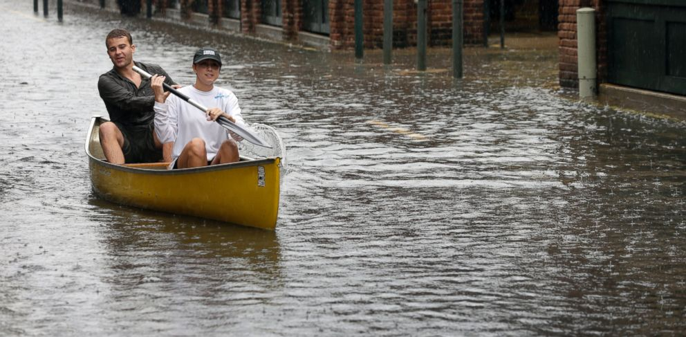 PHOTO: Dillon Christ, front, and Kyle Barnell paddle their canoe down a flooded street in Charleston, S.C., Saturday, Oct. 3, 2015.