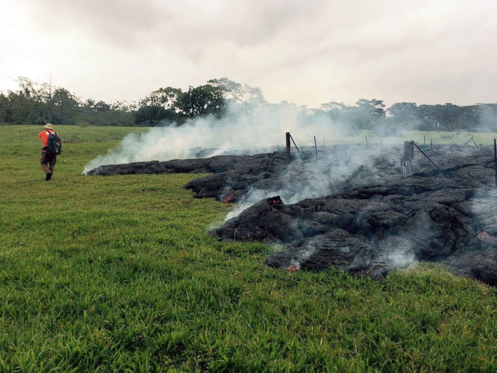 PHOTO: A Hawaii Volcano Observatory geologist maps the margin of the June 27 lava flow in the open field below Cemetery Road near the town of Pahoa on the Big Island of Hawaii, Oct. 26, 2014.