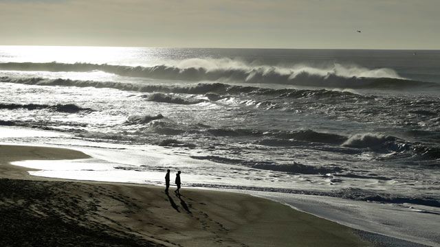 PHOTO: A couple walk along the North Beach as a helicopter searches for a man lost in the high surf, Jan. 1, 2013, at the Point Reyes National Seashore, Calif.