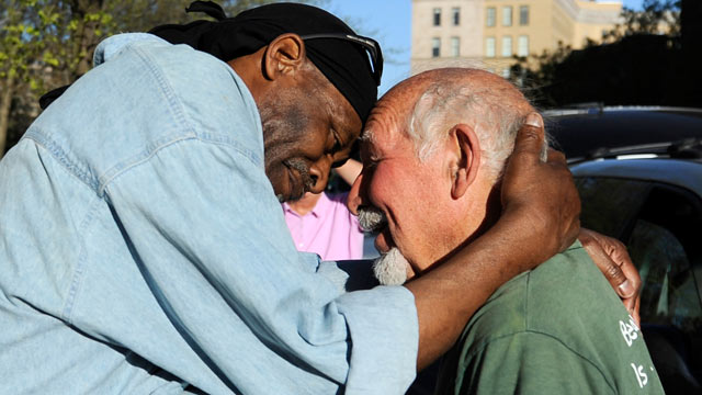PHOTO: Michael Johnson, left, hugs friend Anthony Cymerys, known as Joe the Barber, in Bushnell Park in Hartford, Conn on May 1, 2013.