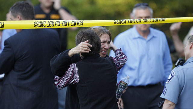 PHOTO: An unidentified woman is consoled at the scene of a shooting that left at least two dead and four others wounded at Accent Signage Systems in Minneapolis, Thursday, Sept. 27, 2012.