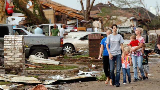 PHOTO: People walk through a neighborhood south of SW 149th between Western and Hudson after a tornado struck south Oklahoma City and Moore, Okla., May 20, 2013.