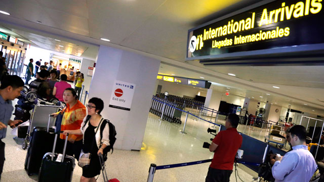 PHOTO: Airline passengers arriving from Hong Kong walk from the international arrivals area at Newark Liberty Airport, June 17, 2013, in Newark, N.J.