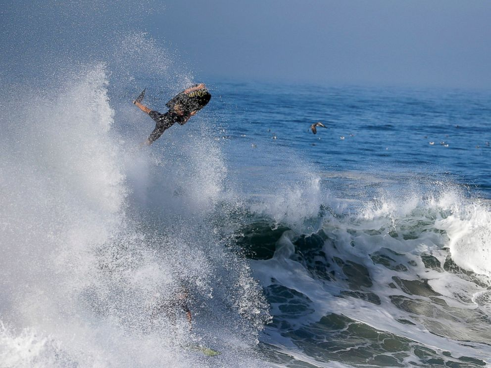 PHOTO: A bogie boarder flies over a wave a surfer rides underneatch a wave at the wedge in Newport Beach, Calif., Aug. 27, 2014.