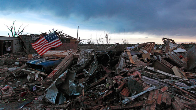 PHOTO: An American flag blows in the wind at sunrise atop the rubble of a destroyed home in Moore, Okla., on May 21, 2013, a day after a tornado roared through the Oklahoma City suburb, flattening entire neighborhoods and destroying an elementary school w