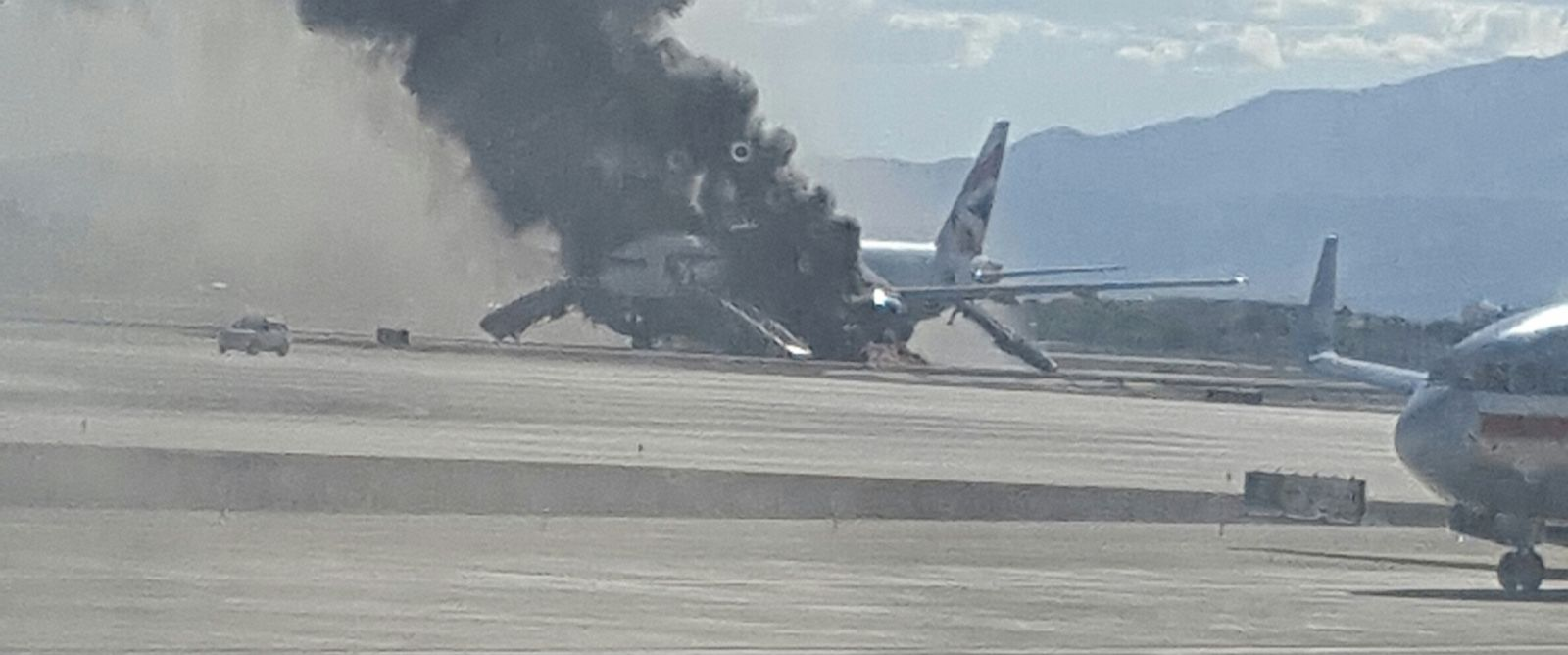 PHOTO: In this photo taken from the view of a plane window, smoke billows out from a plane that caught fire at McCarren International Airport, Tuesday, Sept. 8, 2015, in Las Vegas.