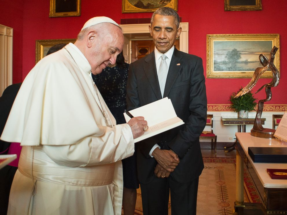 PHOTO: In this photo provided by LOsservatore Romano, Pope Francis signs a guest book as President Barack Obama looks on at the White House in Washington, Sept. 23, 2015.