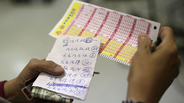 PHOTO: Sharon Long double checks her Powerball numbers as she stands in line in a convenience store in Baltimore, Wednesday, Nov. 28, 2012. Long, a customer service representative for a plumbing company, picked numbers that her sister asked her to play wi