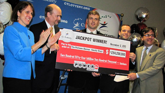 PHOTO: In this photo provided by the Connecticut Lottery, Greenwich, Conn. wealth managers Tim Davidson, second left, Greg Skidmore, center, and Brandon Lacoff, second right, pose, Nov. 28. 2011 with a ceremonial check after the men claimed a $254.2 milli